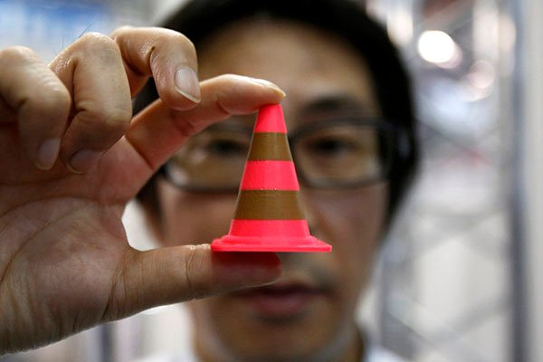 A staff of Nihonbinary shows an Acrylonitrile butadiene styrene pylon which is printed by the 3D printer MakerBot Replicator 2X during the International Robot Exhibition 2013 in Tokyo November 8, 2013. Japanese entrepreneurs are building businesses based on 3D printing, showing the sort of pioneering spirit Prime Minister Shinzo Abe hopes can revitalise a calcified economy. Whether these entrepreneurs can lay the foundations for a new era in Japanese products though may depend on whether Abe can tear down barriers in a wider business culture that shuns risk and supports the status quo. Picture taken November 8, 2013. To match story JAPAN-ECONOMY/3DPRINTER   REUTERS/Yuya Shino (JAPAN - Tags: BUSINESS)