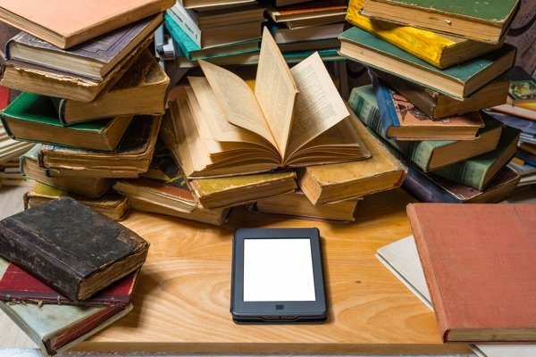 E-reader surrounded by books