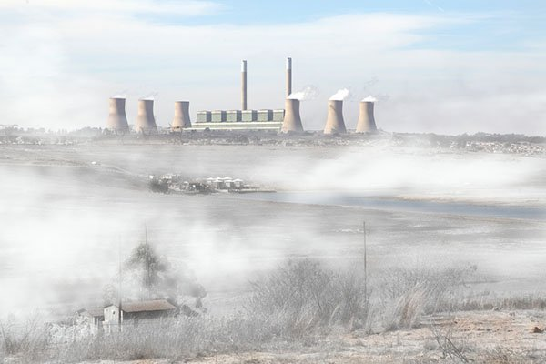 Air pollution in a coal rich South Africa. Chimneys billowing with toxic smoke on an early winters morning